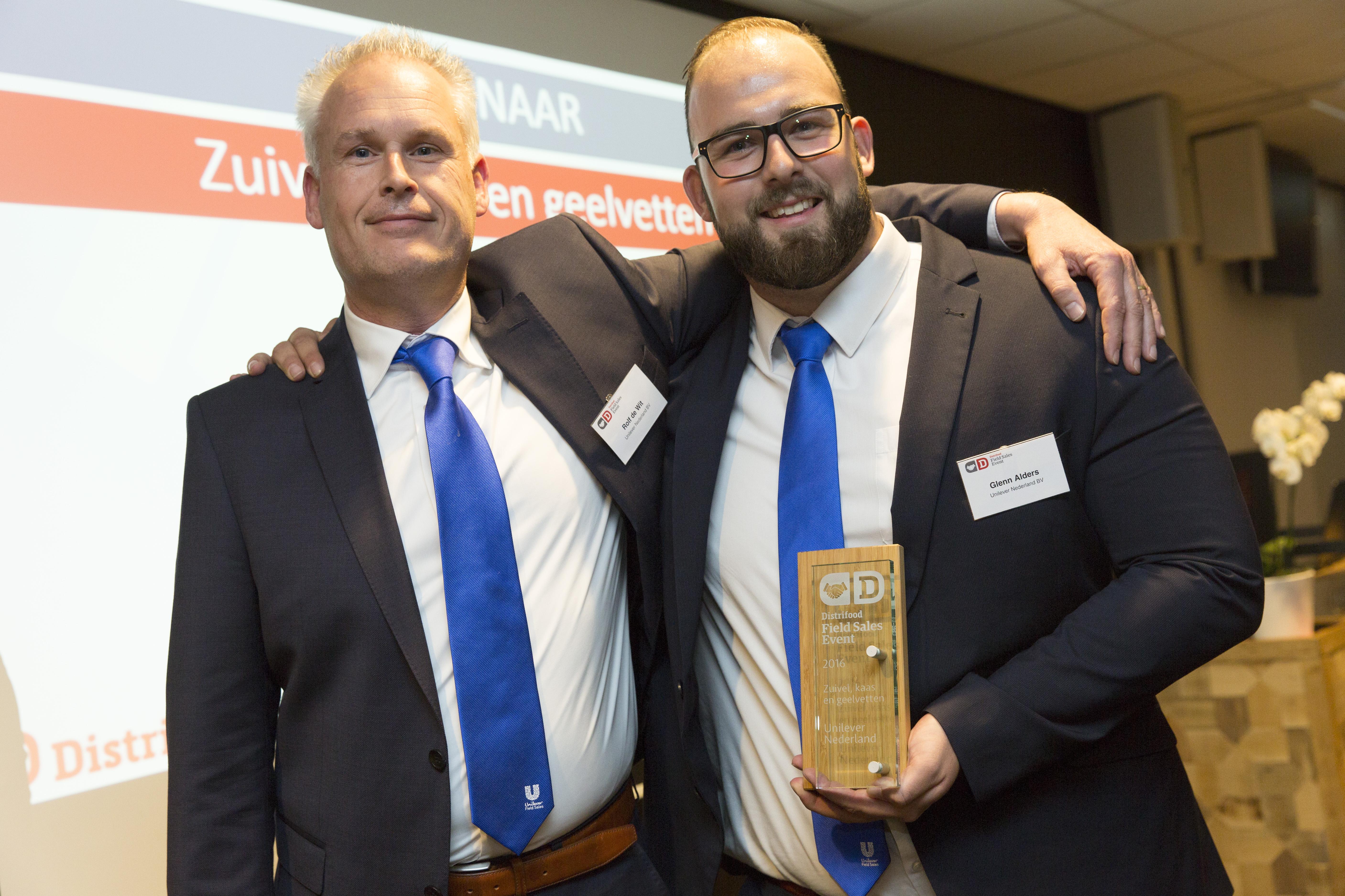 Rolf de Wit (l), senior rayonmanager, en Glenn Alders, eveneens senior rayonmanager. Namens hun collega's poseren zij trots met de bokaal voor de overwinning in de categorie zuivel, kaas en geelvetten