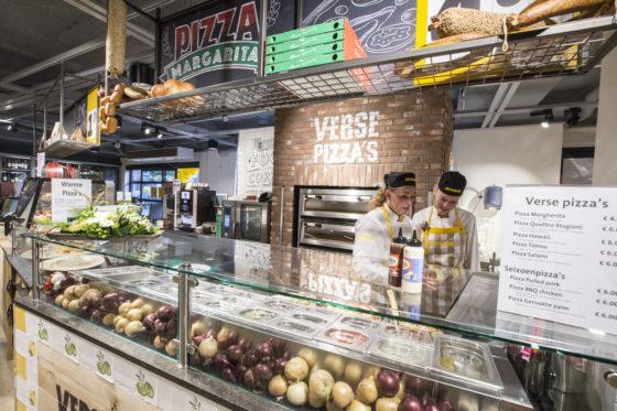 Nog steeds achter de kassa's, verse pizza's die warm of koud kunnen worden meegenomen.  Ook zijn hier koffie en gebak verkrijgbaar. Foto: Koos Groenewold.